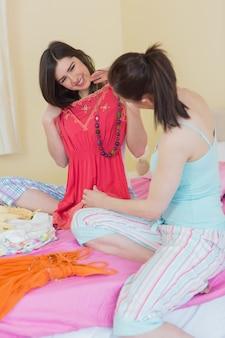 Heureuse filles regardant une robe à une soirée pyjama