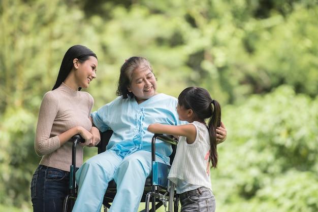 Heureuse grand-mère en fauteuil roulant avec sa fille et son petit-fils dans un parc, happy life happy time.