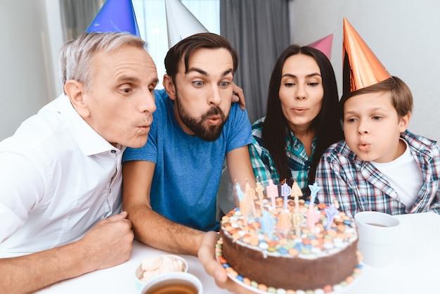 Heureuse grande famille avec des chapeaux de vacances souffler des bougies.