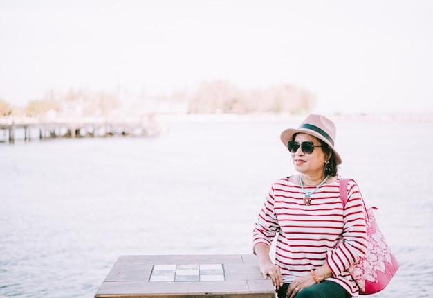Heureuse haute femme asiatique assise à l'extérieur