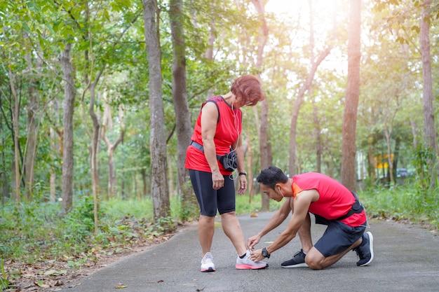 Heureuse haute femme asiatique avec homme ou entraîneur personnel attachant des lacets de chaussure dans le parc
