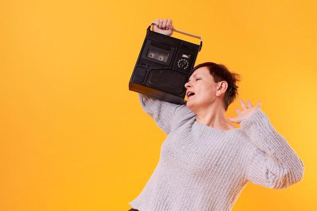 Heureuse haute femme écoutant de la musique à partir d'un lecteur de cassette