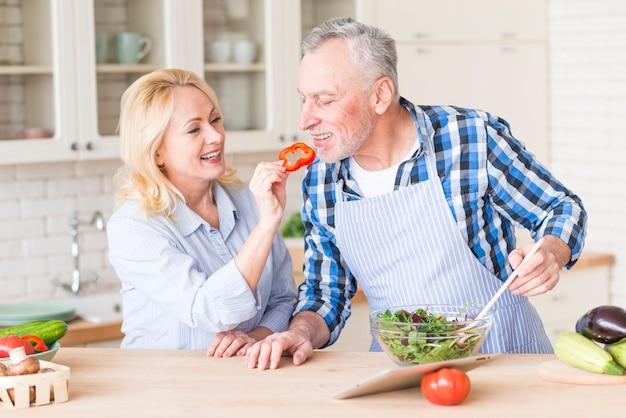 Heureuse haute femme mange une tranche de poivron rouge à son mari préparant la salade dans la cuisine