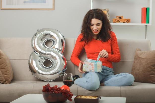 Heureuse et heureuse jeune femme dans des vêtements décontractés souriant joyeusement assis sur un canapé avec ballon en forme de numéro huit tenant présent va l'ouvrir pour célébrer la journée internationale de la femme le 8 mars