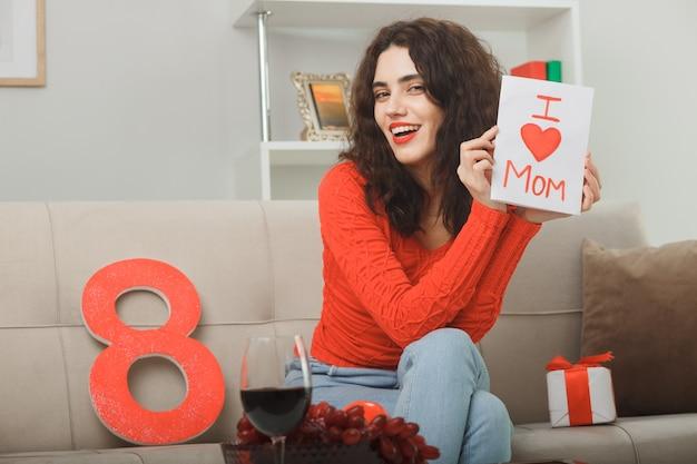 Heureuse et heureuse jeune femme en vêtements décontractés assis sur un canapé avec numéro huit et présent tenant une carte de voeux souriant joyeusement célébrant la journée internationale de la femme le 8 mars