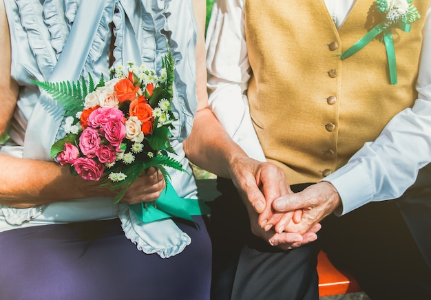 Heureuse histoire d'amour de couple de personnes âgées. un vieux couple est assis sur un banc dans le parc verdoyant. grand-mère et grand-père se tenant la main. mode de vie des personnes âgées.