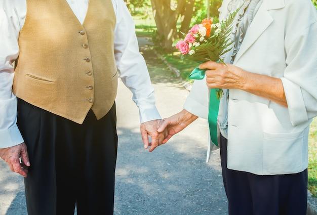 Heureuse histoire d'amour de couple de personnes âgées. un vieux couple marche dans le parc verdoyant. grand-mère et grand-père en riant. mode de vie des personnes âgées. ensemble les retraités.