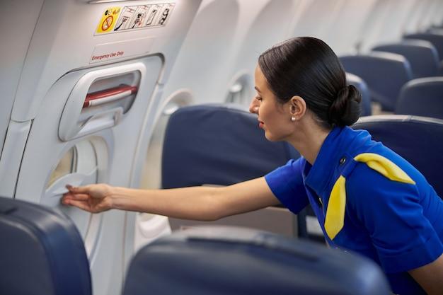 Heureuse hôtesse de l'air professionnelle prépare le salon avant le vol de nuit