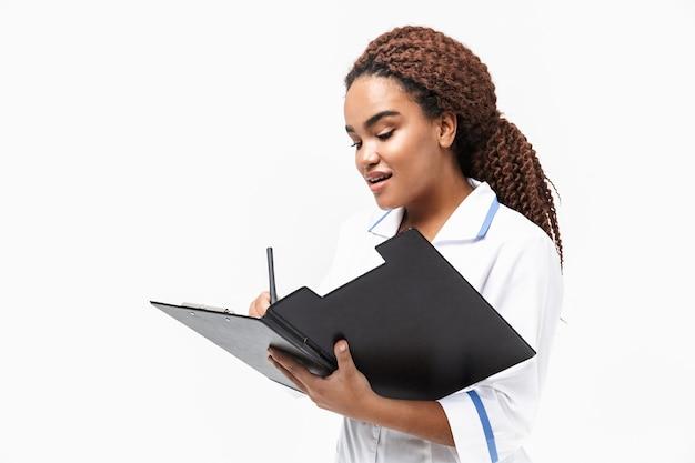Heureuse infirmière écrivant un rapport de cas médical isolé contre un mur blanc