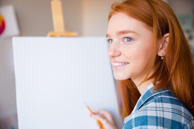 Heureuse jeune artiste femme reahead en chemise à carreaux faisant des croquis sur toile en classe d'art