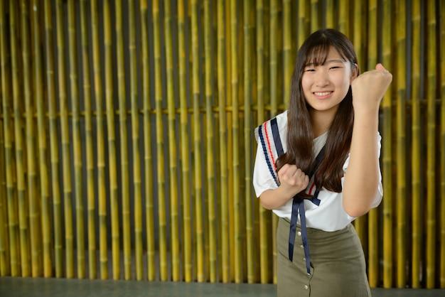 Heureuse jeune belle adolescente asiatique contre une clôture en bambou