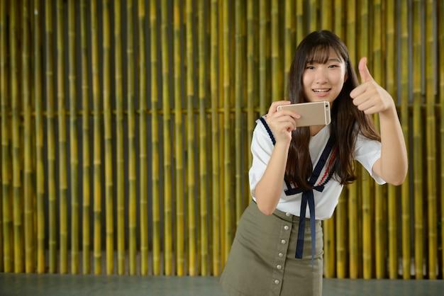 Heureuse jeune belle adolescente asiatique prenant une photo avec un téléphone contre une clôture en bambou