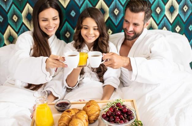 Heureuse jeune belle famille en peignoirs prennent le petit déjeuner le matin dans une chambre d'hôtel de luxe