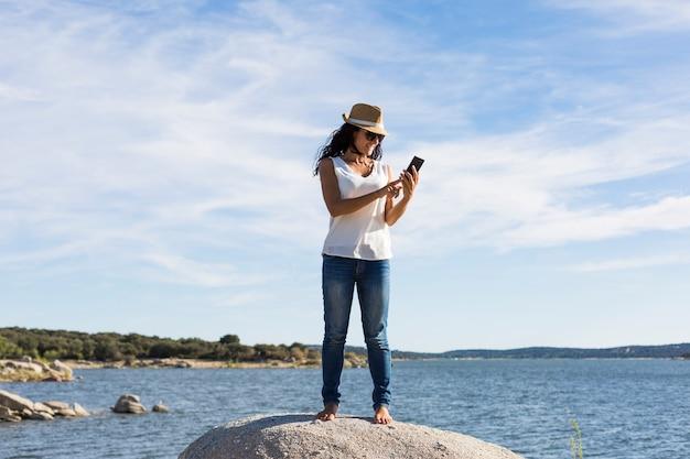 Heureuse jeune belle femme à l'aide de téléphone portable à la plage. le coucher du soleil. mode de vie
