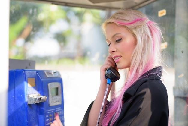 Heureuse jeune belle femme blonde parlant au téléphone public dans les rues à l'extérieur