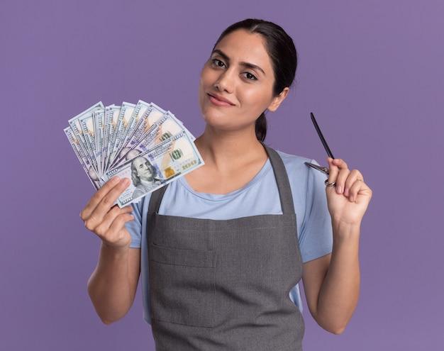 Heureuse jeune belle femme coiffeur en tablier tenant de l'argent et des ciseaux à l'avant avec le sourire sur le visage debout sur le mur violet