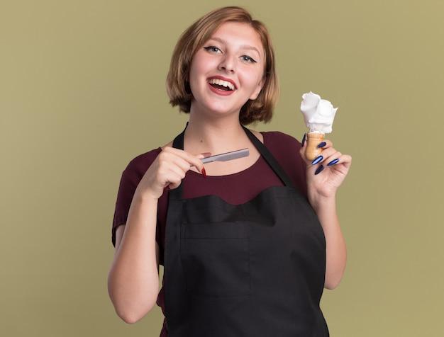 Heureuse jeune belle femme coiffeur en tablier tenant le rasoir et le blaireau avec de la mousse à raser à l'avant avec le sourire sur le visage debout sur le mur vert