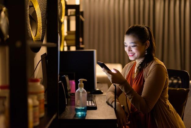 Heureuse jeune belle femme indienne à l'aide de téléphone et de travail à domicile tard dans la nuit