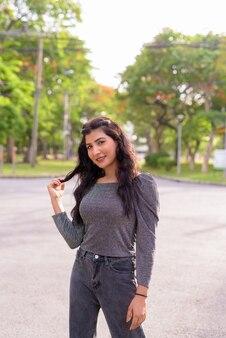 Heureuse jeune belle femme indienne souriante dans les rues du parc