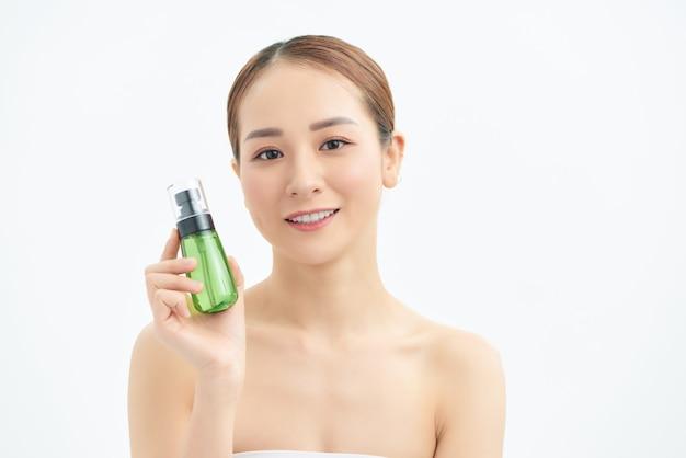Heureuse jeune belle femme montrant une bouteille cosmétique sur fond blanc.