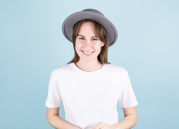 Heureuse jeune belle femme portant un chapeau gris avec chemise blanche, regardant la caméra et souriant sur fond bleu.