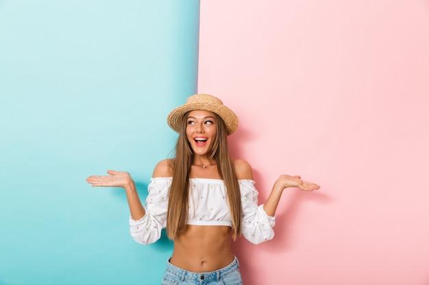 Heureuse jeune belle femme posant isolé portant un chapeau montrant la surface.