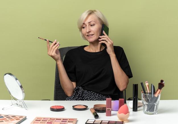 Heureuse jeune belle fille assise à table avec des outils de maquillage parle au téléphone tenant un pinceau de maquillage isolé sur un mur vert olive