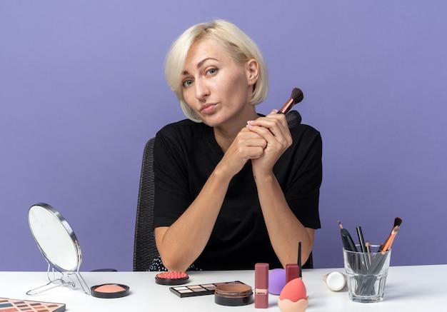 Heureuse jeune belle fille assise à table avec des outils de maquillage tenant des pinceaux à poudre isolés sur un mur bleu