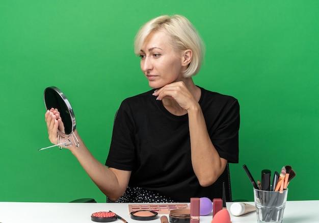 Heureuse jeune belle fille assise à table avec des outils de maquillage tenant et regardant un miroir mettant la main sous le menton isolé sur un mur vert