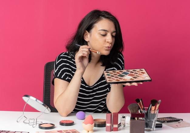 Heureuse jeune belle fille assise à table avec des outils de maquillage tenant et regardant une palette de fards à paupières avec un pinceau de maquillage isolé sur un mur rose