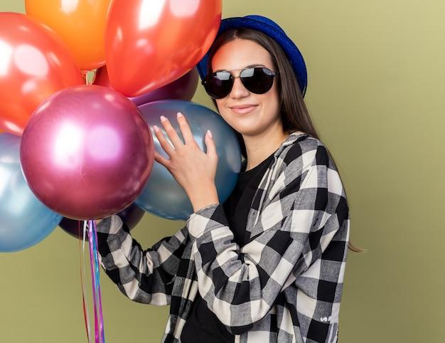 Heureuse jeune belle fille portant un chapeau bleu avec des lunettes tenant des ballons isolés sur un mur vert olive