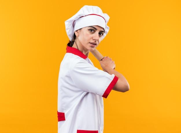 Heureuse jeune belle fille en uniforme de chef tenant un rouleau à pâtisserie isolé sur un mur orange