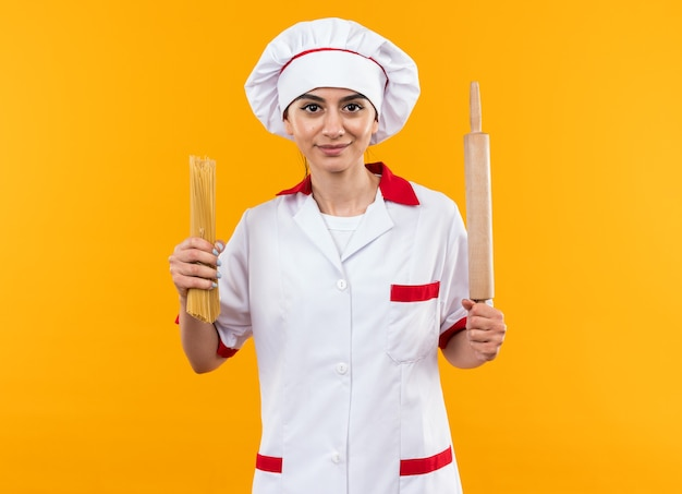 Heureuse jeune belle fille en uniforme de chef tenant des spaghettis avec un rouleau à pâtisserie isolé sur un mur orange
