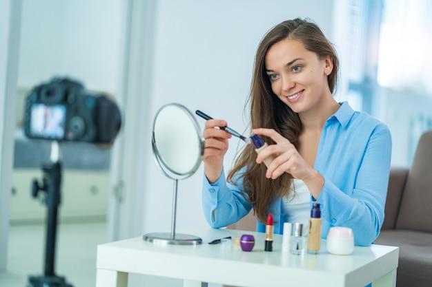 Heureuse jeune blogueuse femme souriante tenant la brosse et le fond de teint lors de l'enregistrement de son blog beauté sur le maquillage et les cosmétiques à la maison.