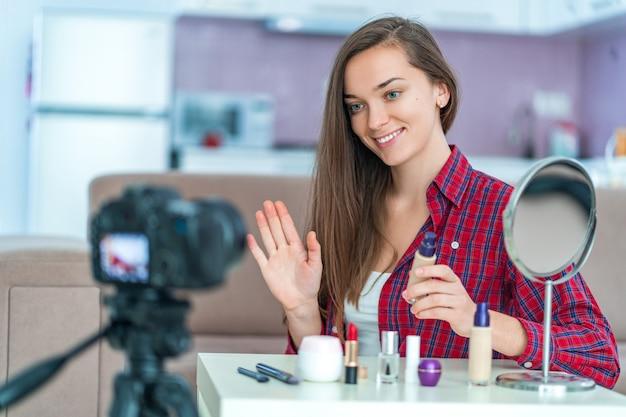Heureuse jeune blogueuse vidéo souriante pendant une diffusion en direct avec son public et un blog de beauté sur le maquillage et les cosmétiques à la maison. blogging