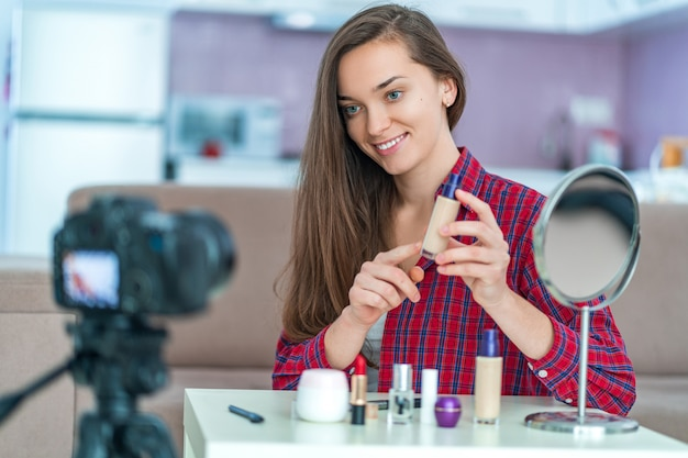 Heureuse jeune blogueuse vidéo souriante tient et montre les fondations au public lors de l'enregistrement de son blog beauté sur le maquillage et les cosmétiques à la maison. blogging