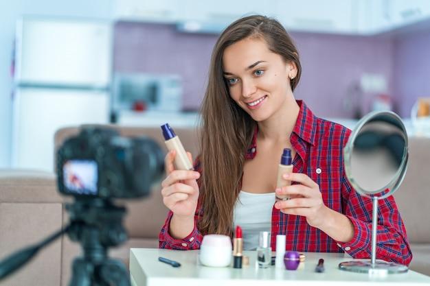 Heureuse jeune blogueuse vidéo souriante tient et montre les fondations au public lors de l'enregistrement de son blog beauté sur le maquillage et les cosmétiques à la maison. bloguer et travailler en freelance
