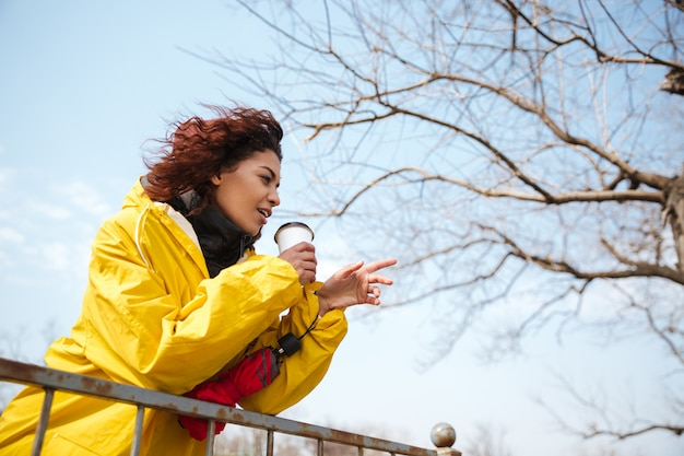 Heureuse jeune bouclée africaine portant un manteau jaune, boire du café.