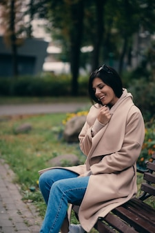 Heureuse jeune brune assise sur un banc de parc