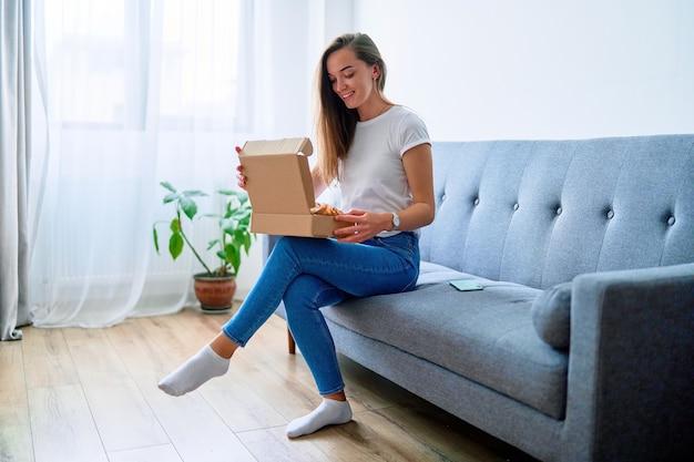 Heureuse jeune cliente accro du shopping satisfaite et joyeuse assise sur un canapé à la maison et ouvrant la boîte de colis en carton reçue, concept de livraison de commerce de service facile et rapide