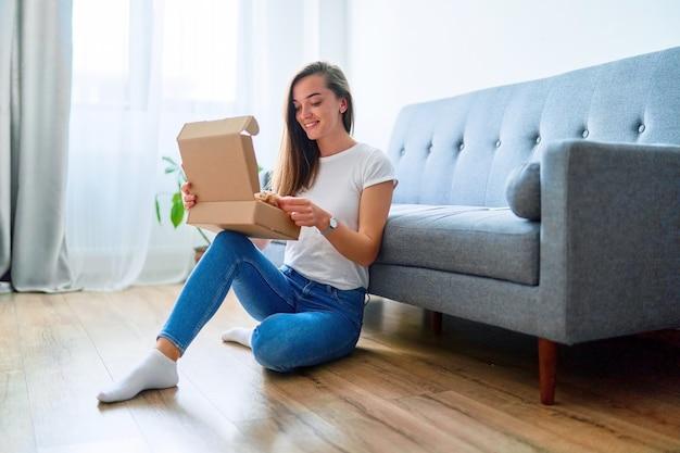 Heureuse jeune cliente accro du shopping satisfaite et joyeuse assise sur un sol à la maison et ouvrant la boîte de colis en carton reçue après la commande en ligne, concept de livraison de commerce de service facile et rapide