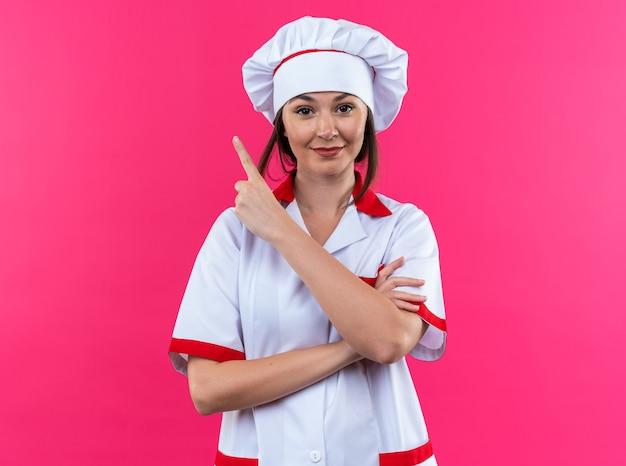 Heureuse jeune cuisinière portant des points uniformes de chef sur le côté isolé sur un mur rose avec espace de copie