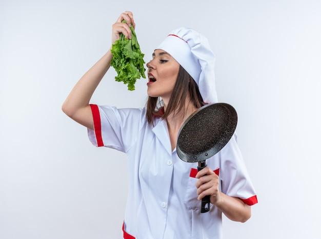 Heureuse jeune cuisinière portant l'uniforme du chef tenant une salade avec une poêle à frire isolée sur un mur blanc