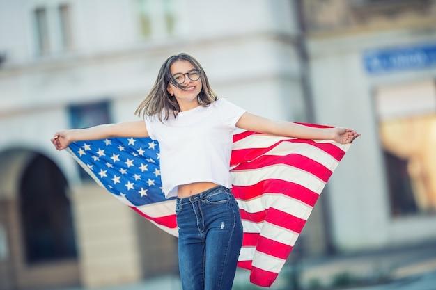 Heureuse jeune écolière américaine tenant et agitant dans la ville avec le drapeau américain.