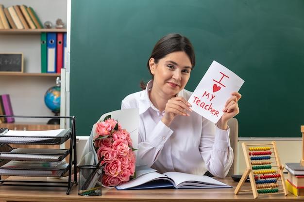 Heureuse jeune enseignante tenant une carte de voeux assise à table avec des outils scolaires en classe