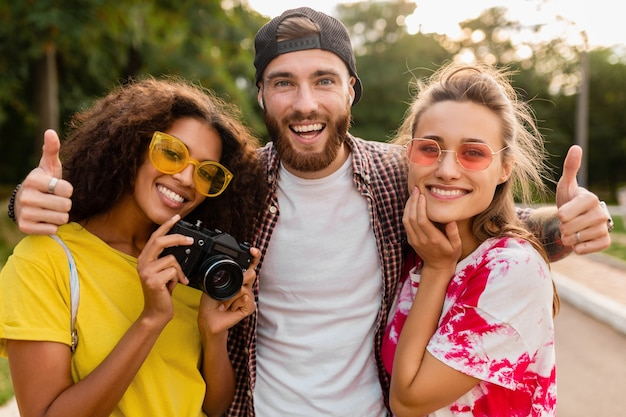 Heureuse jeune entreprise d'amis souriants émotionnels marchant dans le parc avec appareil photo, homme et femme s'amusant ensemble