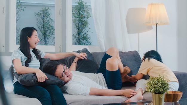 Heureuse jeune famille asiatique joue ensemble sur le canapé à la maison. chinois mère père et fille enfant bénéficiant heureux se détendre passer du temps ensemble dans le salon moderne en soirée.
