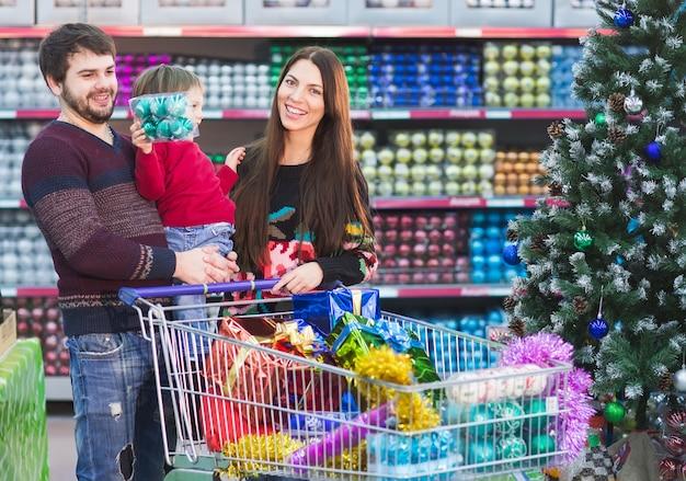 Heureuse jeune famille au supermarché choisit des cadeaux pour la nouvelle année.