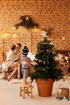 Heureuse jeune famille dans la chambre décore le sapin de noël