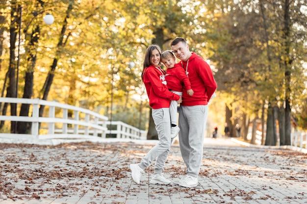 Heureuse jeune famille dans le parc en automne. maman, papa et petite fille profitant de la vie ensemble à l'extérieur.
